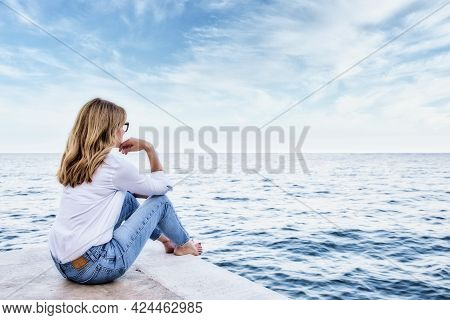 Full Length Shot Of Middle Aged Woman Wearing White Shirt And Blue Jeans While Sitting At The Sea An