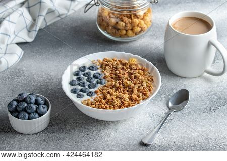 Granola With Yogurt And Coffee On A Gray Table. Hot Morning Drink. Muesli And Blueberries In A White