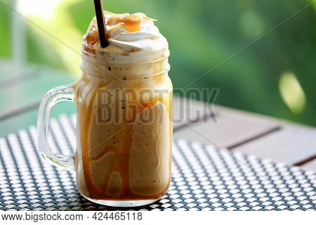 Closeup Iced Coffee Caramel Macchiato Frappe With Whipping Cream On Top In The Mug Glass On Wooden T