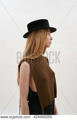 Seductive Young Caucasian Woman Wearing Dark Hat Posing Sideways On White Background, Vertical Shot.
