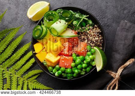Poke bowl with salmon, cucumber and mango. Traditional hawaiian meal. Top view flat lay