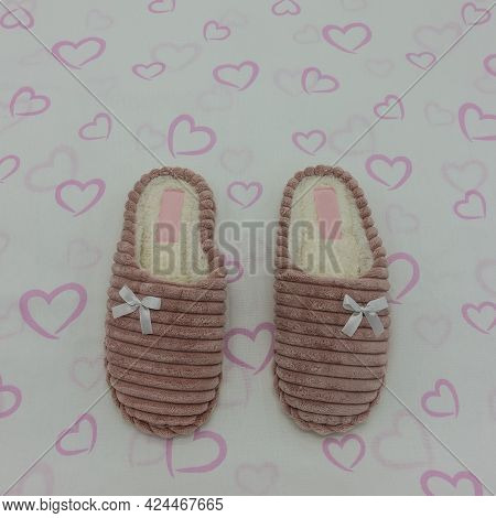 Soft Warm Pink Plush Indoor Slippers. Decorated With Bows. The Background Is White With Hearts. Top