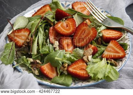 Salad With Strawberries, Nuts On A Concrete Background