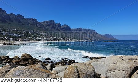 Camps Bay Beach In Cape Town. Turquoise Waves Foaming In The Sand. The Mountain Range Of The Twelve