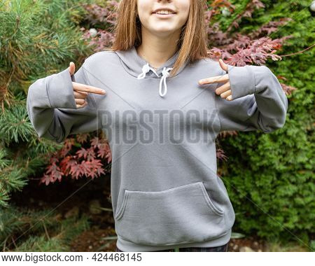 Fashion mockup, grey hoodie with copy space for logo, inscription or design. Young unrecobnizable teenage girl wears sweatshirt outdoor, she stands in front od camera.