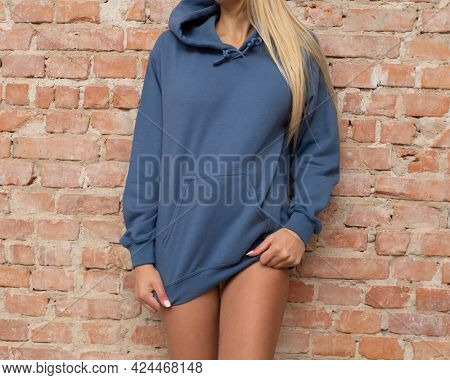 Hoodie mockup. Unrecognizable woman wears blue hoodie. There is a place on hoodie for inscription or design for fashion mockup. Casual outfit for lady.