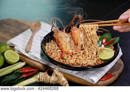 Spicy Instant Noodles Soup And Rivers Shrimp With Hand And Chopsticks, On Black Table Background. To