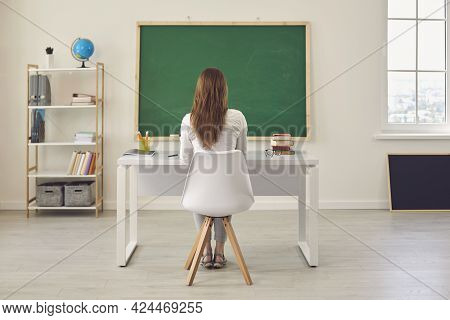 Back View. Young Woman Teacher Sitting At The Table In The Classroom Of The College Lyceum School.