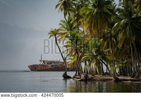 Sink Wrecked, Rusty Ship Lie Down In The Sea Near Tropical Island With Palm Tree. Concept Of Adventu