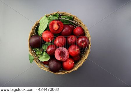 Red Ripe Plums In A Wicker Basket On A Gray Background. Whole Plums And Halves Of Red Juicy Plums Wi