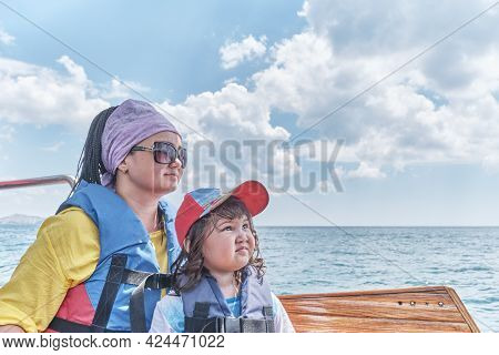 An Asian Little Girl In Baseball Cap, Life Jacket And Her Mother Trip On Pleasure Boat On The Sea. T