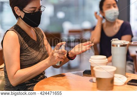 Woman In Protective Mask Spray Her Hands With Antiseptic Spray In Cafe