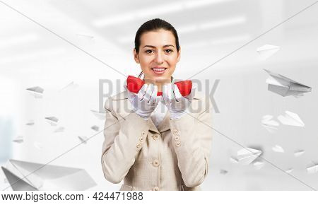 Smiling Young Woman Holding Retro Red Phone In Office With Flying Paper Planes. Call Center Operator