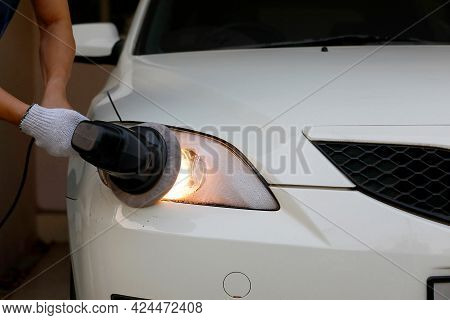 Car Headlight Cleaning With Electric Polishing Machine By Hand Of Worker Man At The White Car.