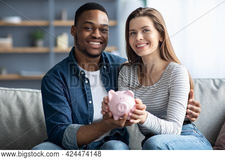 Happy Young Interracial Couple Holding Pink Piggybank And Smiling At Camera