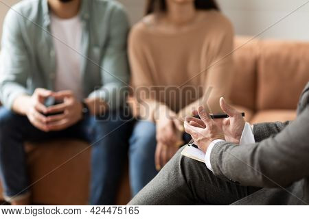 Couple Talking At Session With Male Therapist