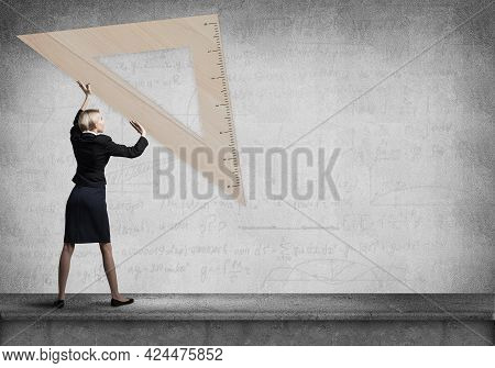 Woman Holding Big Ruler On Wall Background. Testing And Examination Concept. Businesswoman Measuring