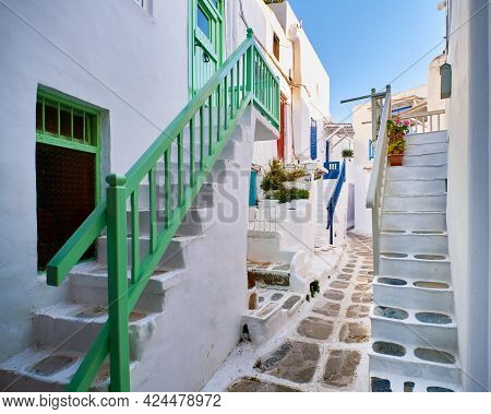 Romantic Traditional Narrow Alleyways Of Greek Island Towns. White Houses, Flower Pots, Colorful Bal