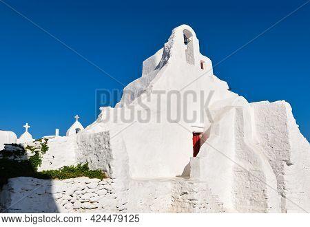 Iconic Tourist Landmark, Mykonos, Greece. White Greek Orthodox Church Of Panagia Paraportiani, Town