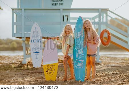 Two Young Pretty Blond Girls In Summer Shorts And Sweaters Posing With Surfboards Against Blue Lifeg