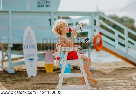 Young Pretty Curly Boy Sitting On High White Chair With Lifeline And Posing With Megaphone On The Be