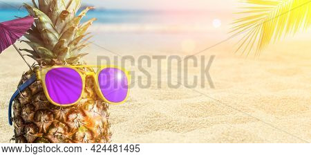 Summer Tropical Pineapple Background. Pineapple In Sunglasses Under A Palm Tree On A Beach Backgroun