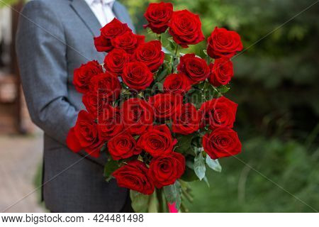 Man In Business Suit Is Holding Big Bouquet Of Red Roses.