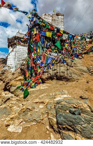 Ruins of Victory Fort Tsemo on the cliff of Namgyal hill and colorful Buddhist prayer flags with Buddhism mantra written on them. Leh, Ladakh, Jammu and Kashmir, India