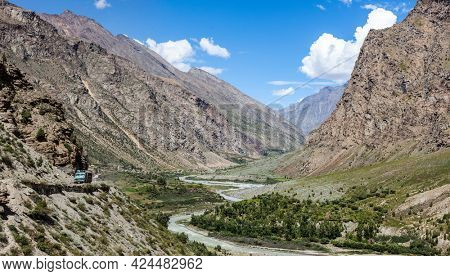 Manali-Leh road in Indian Himalayas with lorry and Chandra river in Lahaul valley. Himachal Pradesh, India
