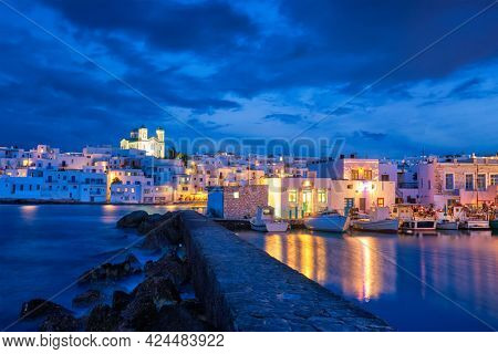 Picturesque view of Naousa town in famous tourist attraction Paros island, Greece with traditional whitewashed houses illuminated in night