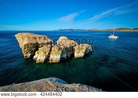White rocks of famous tourist attraction of Milos island Sarakiniko beach and yacht boat at Sarakiniko Beach, Milos island , Greece