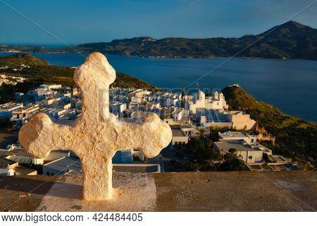 Greek Orthodox Christianity concept background - Christian cross with Plaka village on Milos island in background on sunset. Plaka town, Milos island, Greece. Focus on flowers