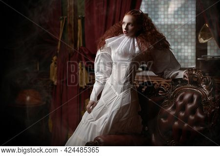 Fashion and history. A sophisticated fashion model girl with lush red hair with fine curls poses in a vintage interior in art dress with a ruffled renaissance collar.
