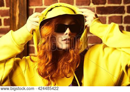 Portrait of a modern young hip-hop dancer girl in yellow hoodie dancing contemporary urban street dance. Brick wall background.