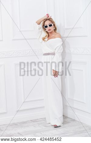Luxury lifestyle. A wealthy middle-aged woman in a chic suit and jewelry poses in a classic white interior. Beauty, fashion.