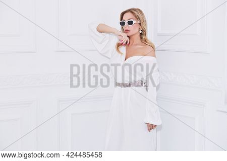 A wealthy middle-aged woman in a chic suit and jewelry poses in a classic white interior. Luxury lifestyle. Beauty, fashion.