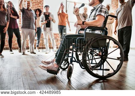 Handicapped man speaking on a microphone in a workshop
