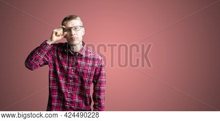 A Male Person In Checkered Shirt Isolated Near The Wall In Eyeglasses And Doing Eye Sight Check Exam