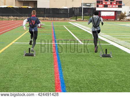 Rear View Of Two High School Track And Field Runners Are Dragging Sleds With Weights For Resistance