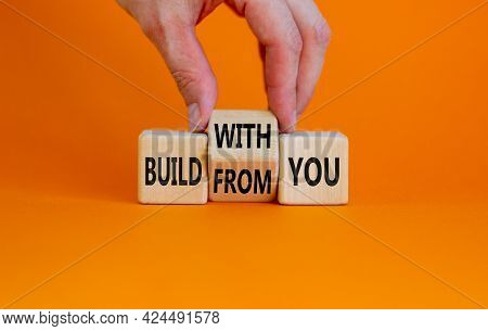 Build From Or With You Symbol. Businessman Turns Wooden Cubes And Changes Words 'build From You' To