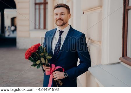 Portrait Of Handsome Bearded Well Dressed Young Man Wearing Blue Suit With Fresh Bouquet Of Roses Wi