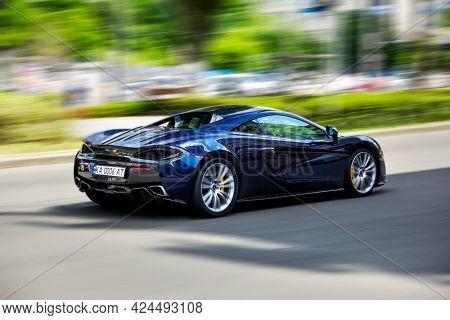 Kiev, Ukraine - June 16, 2021: Blue British Supercar Mclaren 570s In Motion. Blurred Car. Supercar A