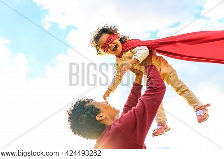 Happy African American Little Fearless Girl Flying Outdoor On Fathers Hands In Summer Park
