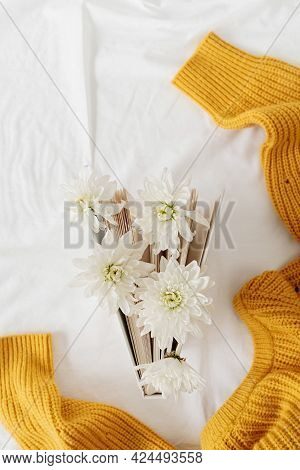 Top View Of A Book With White Chrysanthemum Flowers On White Background With Yellow Sweater
