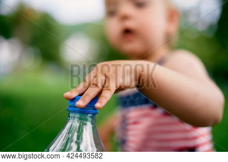 Little Girl In A Striped Dress Unscrews A Bottle Of Water. Close-up