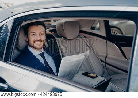 Independent Young Smiling Business Owner In Blue Formal Suit, Sitting In Back Of Limousine, Checking