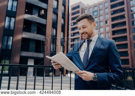 Successful Young Male Economist Reading Business Press In Urban Setting Background, Being Happy With