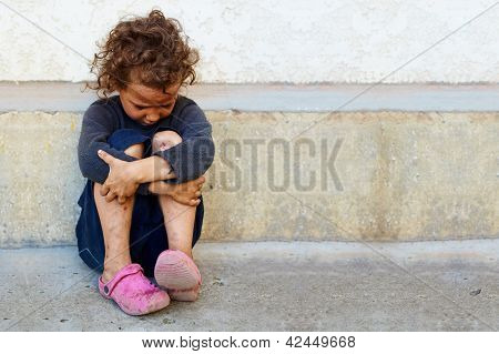 poor sad little child girl sitting against the concrete wall poster