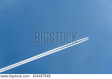 Flying Airoplane On The Blue Sky Leaving White Lines Behind.
