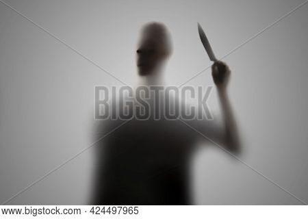 Dark Silhouette Of A Dark Person Holding A Knife, Nightmare Horror Concept, Out Of Focus Blur